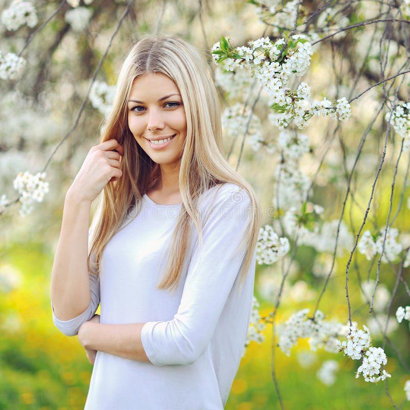 Beautiful young woman in blooming tree in spring royalty free stock photography