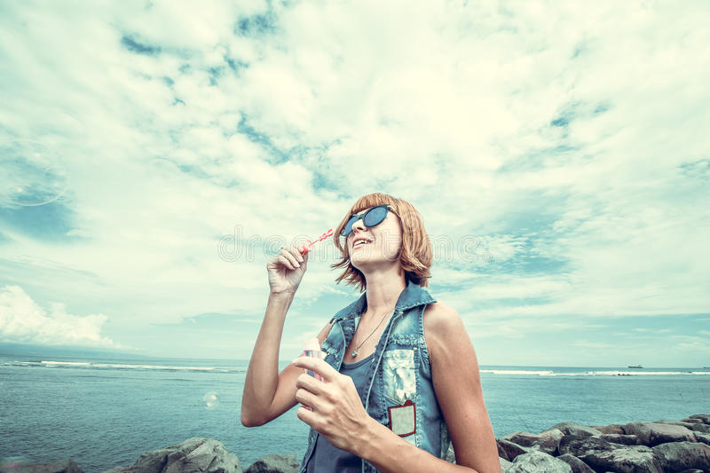 Beautiful young woman blowing bubble in outdoor, nature, near the ocean. Tropical magic island Bali, Indonesia. Beautiful young woman blowing bubble in outdoor royalty free stock images