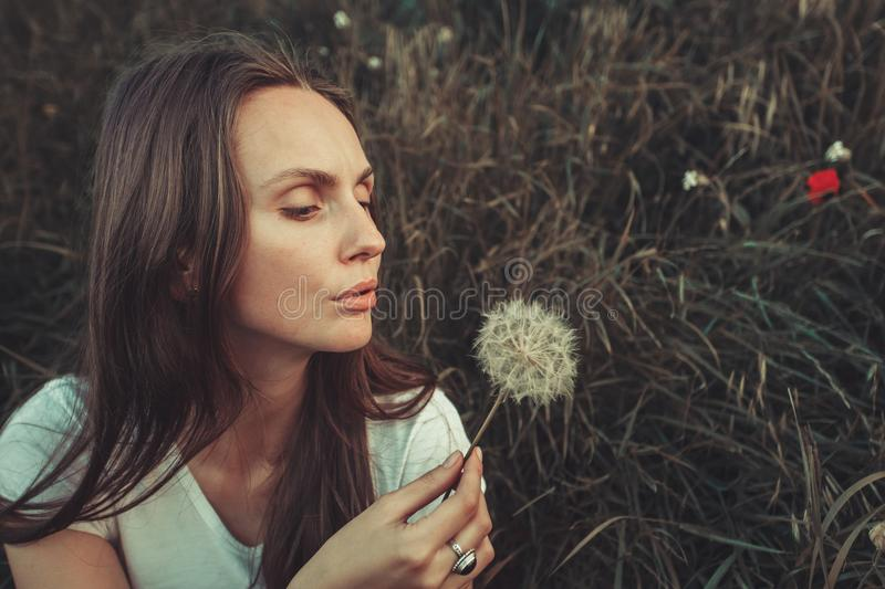 Beautiful Young Woman blowing on dandelion. Beautiful Young Woman sitting in green grass and blowing dandelion. Outdoors. Enjoy Nature. Healthy Caucasian Girl on royalty free stock photo