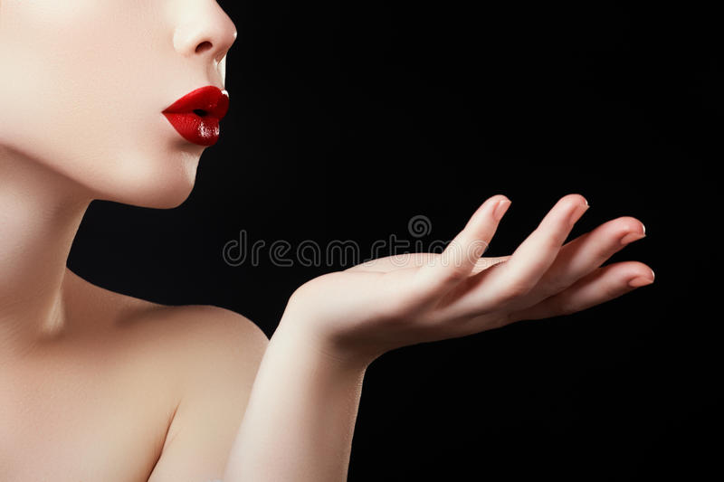 Beautiful young woman blowing a kiss from her hand. Model with perfect dark redl lips and manicured red nails stock photo