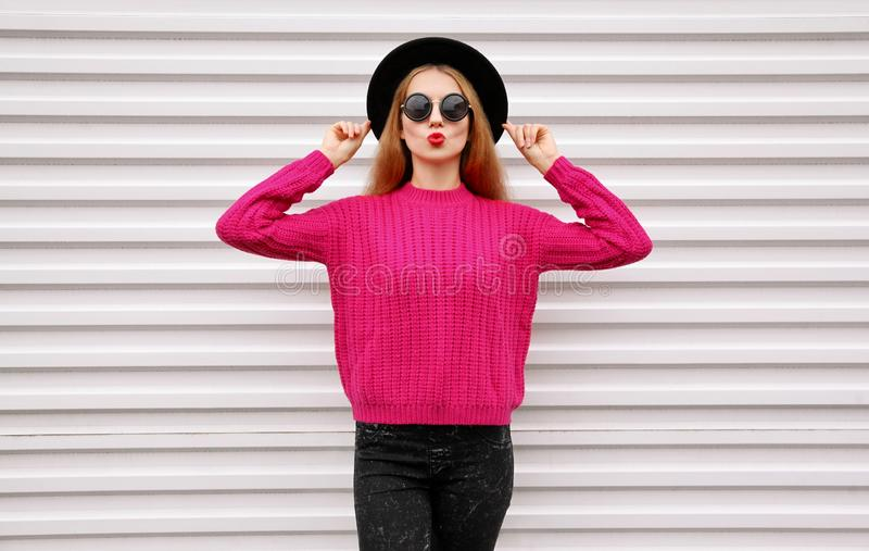 Beautiful young woman blowing red lips sending sweet air kiss in colorful pink knitted sweater stock photography