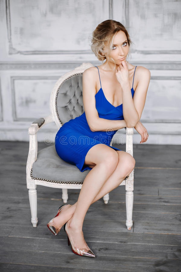 Beautiful young woman in a blue dress and fashionable shoes sitting on a chair in a beautiful interior. stock photography