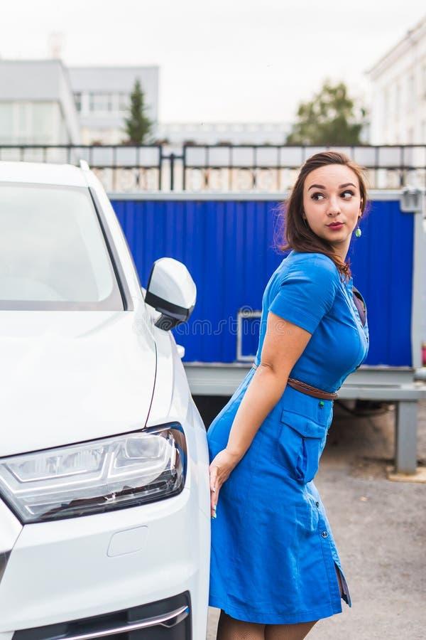 Beautiful young woman in blue dress posing near car stock images