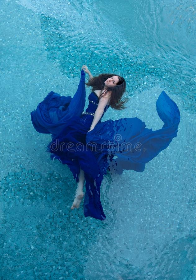 Beautiful young woman in blue evening dress floating weightlessly elegant in the water stock photography