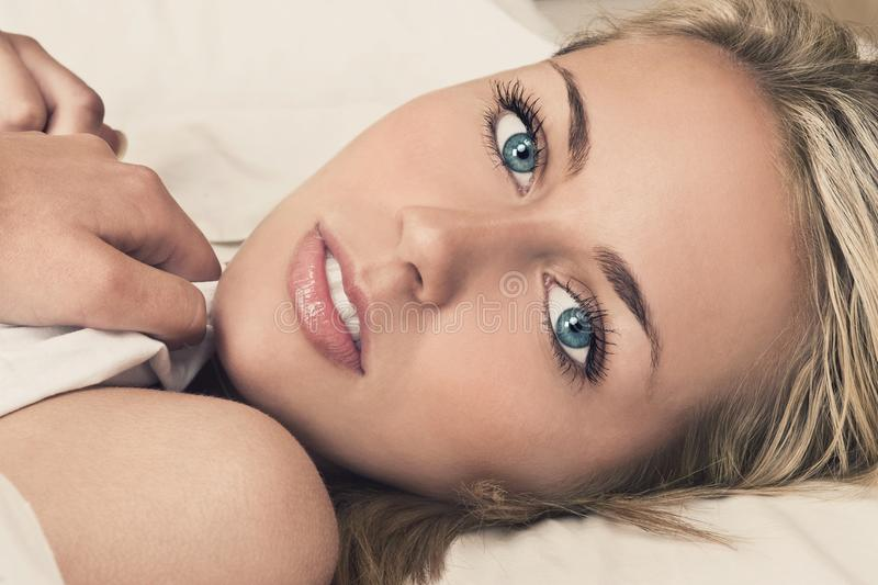 Beautiful Young Woman With Blue Eyes in Bed royalty free stock photography
