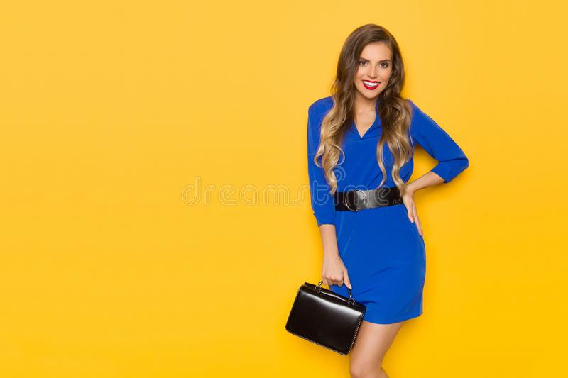 Beautiful Young Woman In Blue Mini Dress Is Posing With Black Leather Bag, Looking At Camera And Smiling stock photos