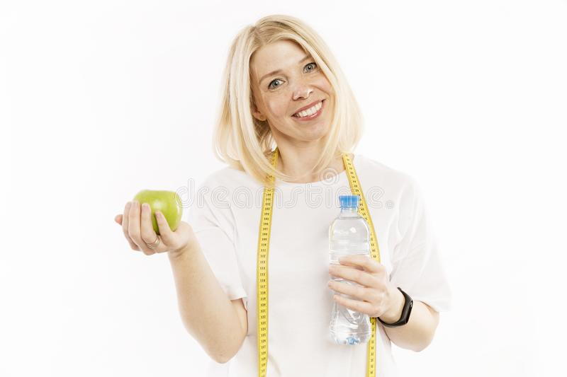 Beautiful young woman with a bottle of water in hands smiling stock photography