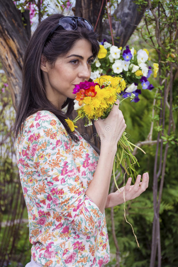 Beautiful young woman with bouquet of flowers in the hands. Portrait of beautiful brunette woman in a spring garden stock photography