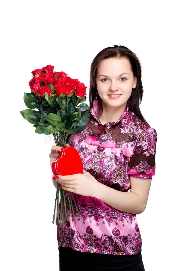 Beautiful young woman with a bouquet of red roses. And heart-shape gift on white stock image