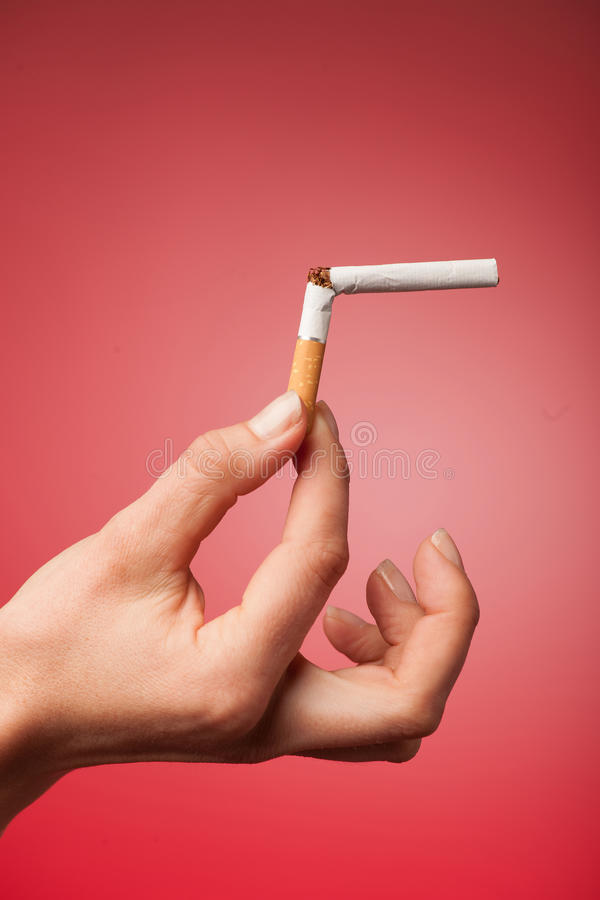 Beautiful young woman breaks a cigarette as a gesture for quit s. Woman holding breaked a cigarette as a gesture for quit smoking unhealthy habbit stock photography