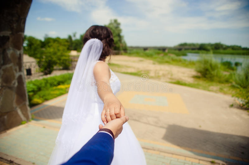 Beautiful young woman bride holds the hand of a man in outdoors. Follow me royalty free stock images