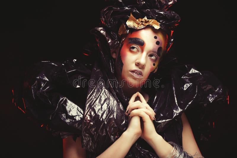 Beautiful young woman with bright fantasy make-up and costume posing on a black background in clouds of smoke. Halloween stock images