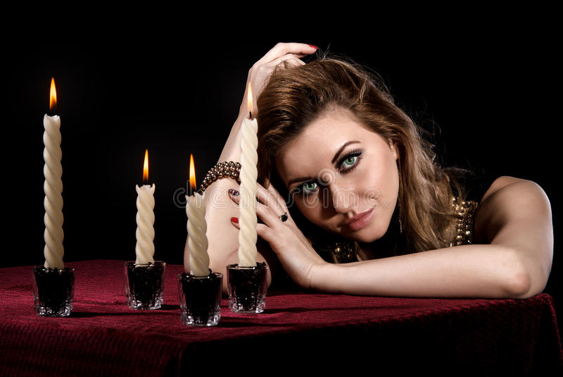Beautiful young woman with bright green eyes near the candles stock photography