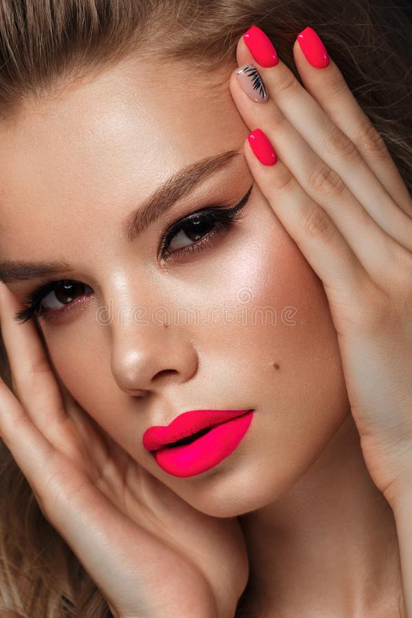 Beautiful young woman with bright makeup and neon pink nails. Beauty face. Photo taken in the studio.  royalty free stock photo