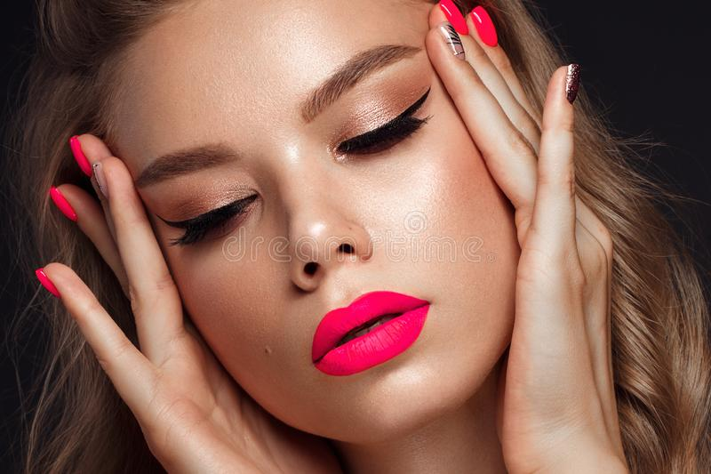 Beautiful young woman with bright makeup and neon pink nails. Beauty face. Photo taken in the studio.  stock photo
