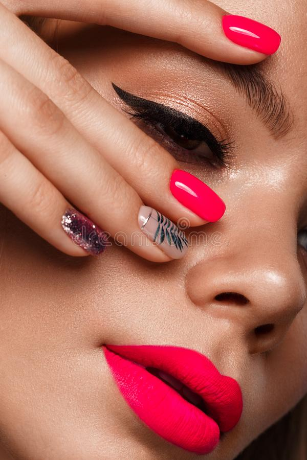 Beautiful young woman with bright makeup and neon pink nails. Beauty face. Photo taken in the studio.  royalty free stock photography