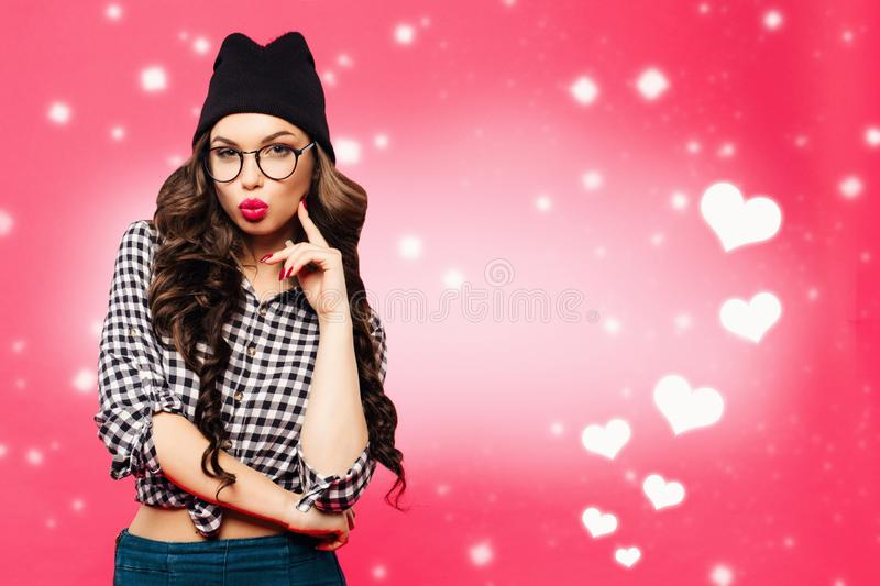Beautiful young woman with bright makeup and pink lips make a kiss holding your finger near the . Hipster girl in hat royalty free stock images