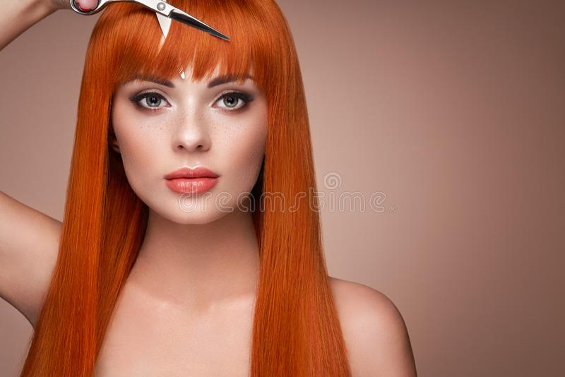 Beautiful young woman with a scissors stock image