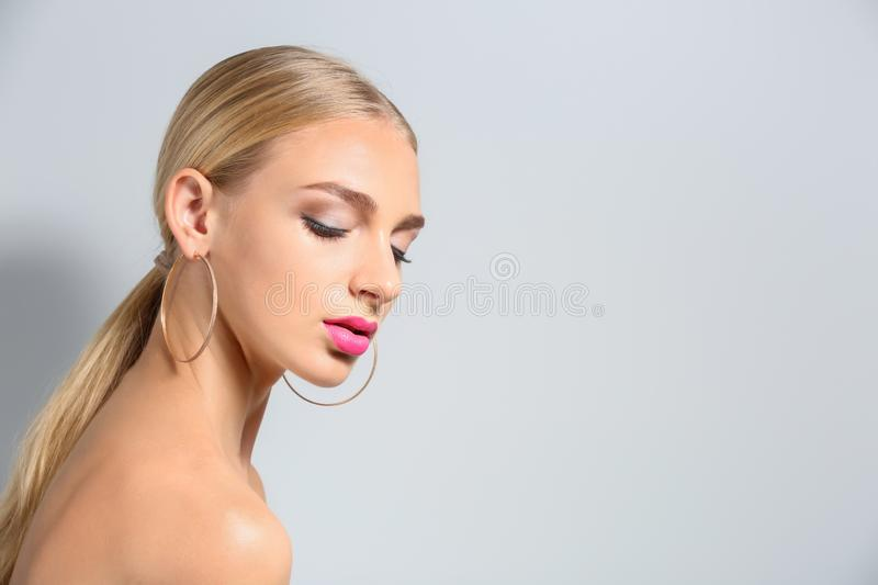 Beautiful young woman with bright pink lipstick on light background stock photos