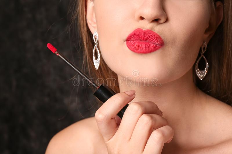 Beautiful young woman with bright red lipstick on dark background, closeup royalty free stock images