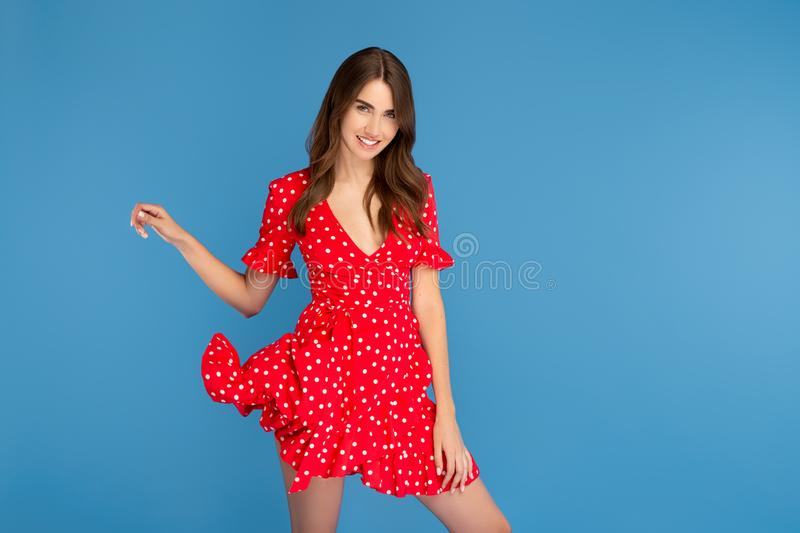 Beautiful young woman with bright smile in red dress over blue background. royalty free stock photography