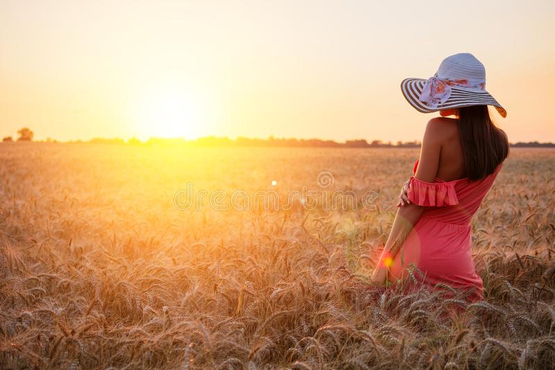 Beautiful young woman with brown hear wearing rose dress and hat enjoying outdoors looking to the sun on perfect wheat field on. Sunset royalty free stock photo