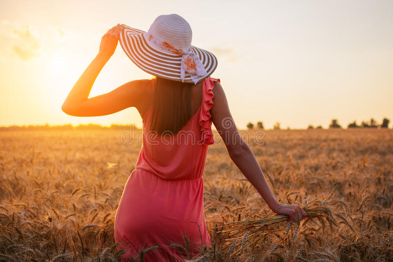 Beautiful young woman with brown hear wearing rose dress and hat enjoying outdoors looking to the sun on perfect wheat field on stock images