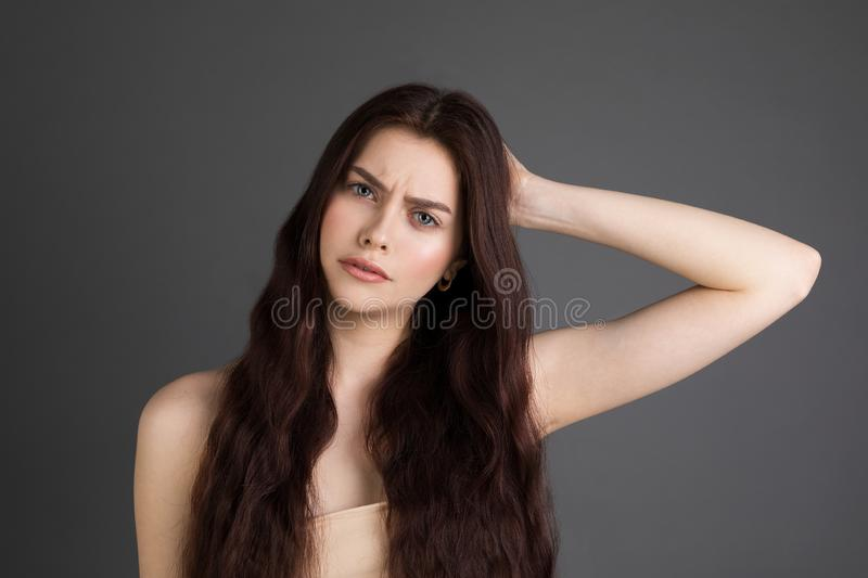 Beautiful young woman with brunette hair suffers from terrible headaches and compresses the head with fingers stock photos