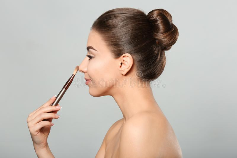 Beautiful young woman with brush for applying makeup on light background stock images
