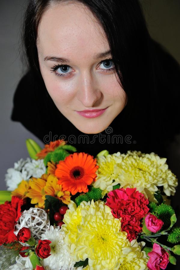 Beautiful young woman with bunch of flowers stock image
