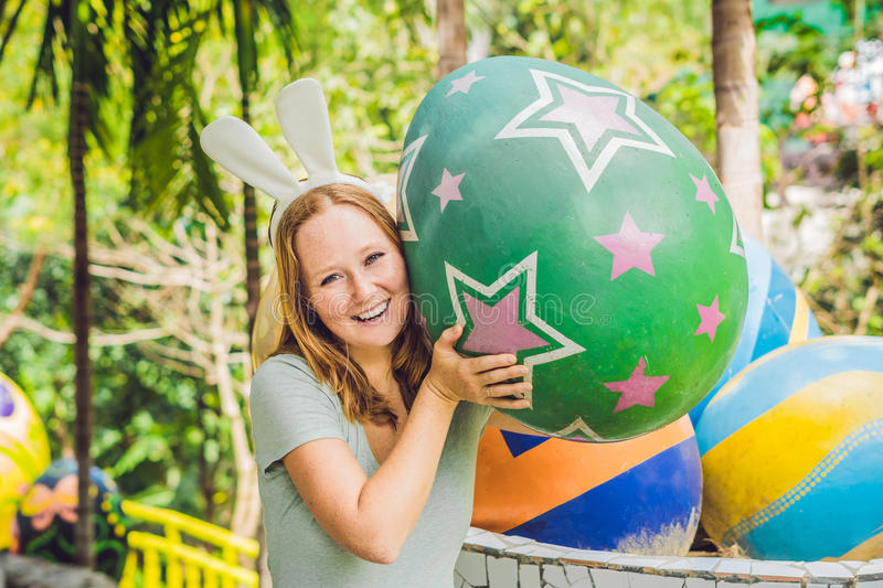 Beautiful young woman with bunny ears having fun with traditional Easter eggs hunt, outdoors. Celebrating Easter holiday.  royalty free stock images
