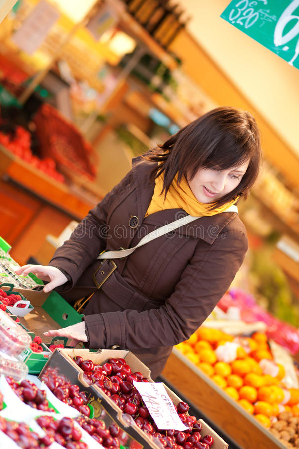 Beautiful young woman buying cherries royalty free stock image