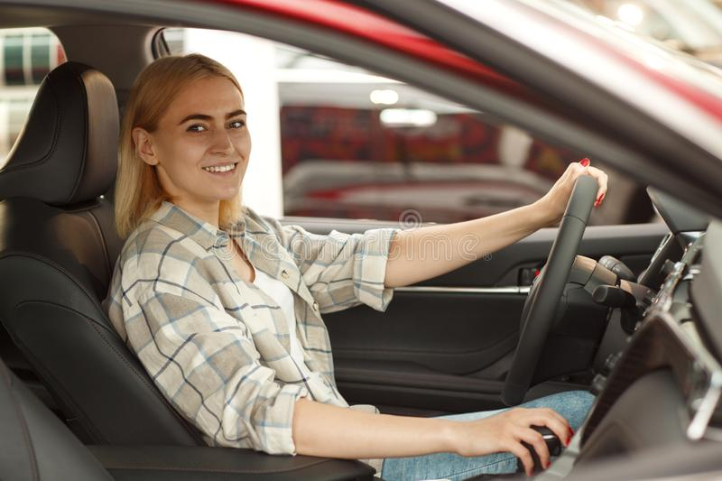 Beautiful young woman buying new car at the dealership royalty free stock photos