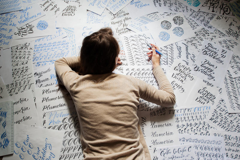 Beautiful young woman calligrapher writing something lying on the floor at living room.  royalty free stock photo