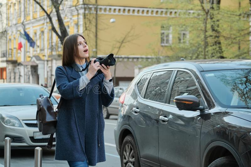Beautiful young woman with camera in city. Tourist girl traveling and photographing, spring city street background stock photography