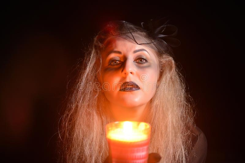 Beautiful young woman with a candle in her hands. Halloween witch concept stock photos