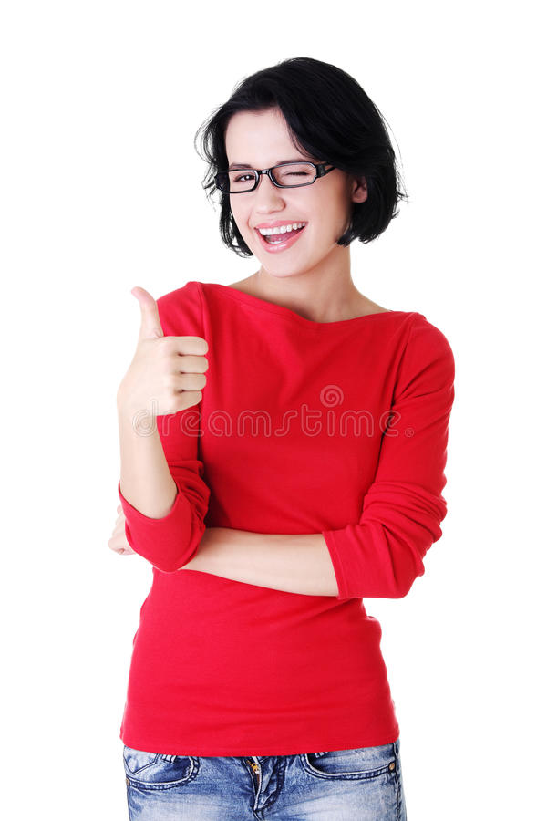 Woman in casual clothes gesturing thumbs up. Beautiful young woman in casual clothes gesturing thumbs up royalty free stock photography