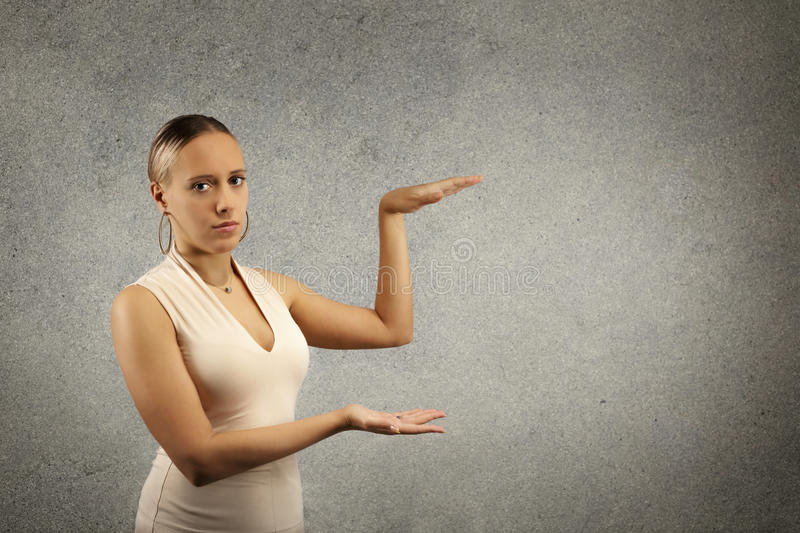 Beautiful young woman in casual cloths showing empty copy space on the open hand palm or with hands stock photography