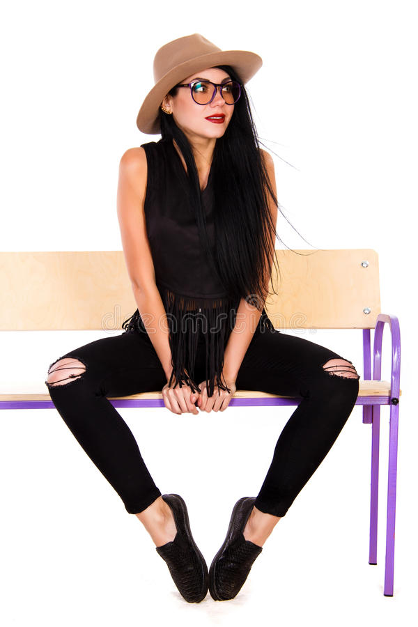 Beautiful young woman in a casual style clothes sitting on a woo royalty free stock photos