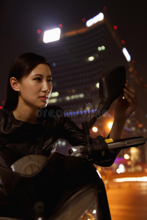 Beautiful young woman checking herself in the side mirror of a motorcycle, outdoors at night in Beijing stock image