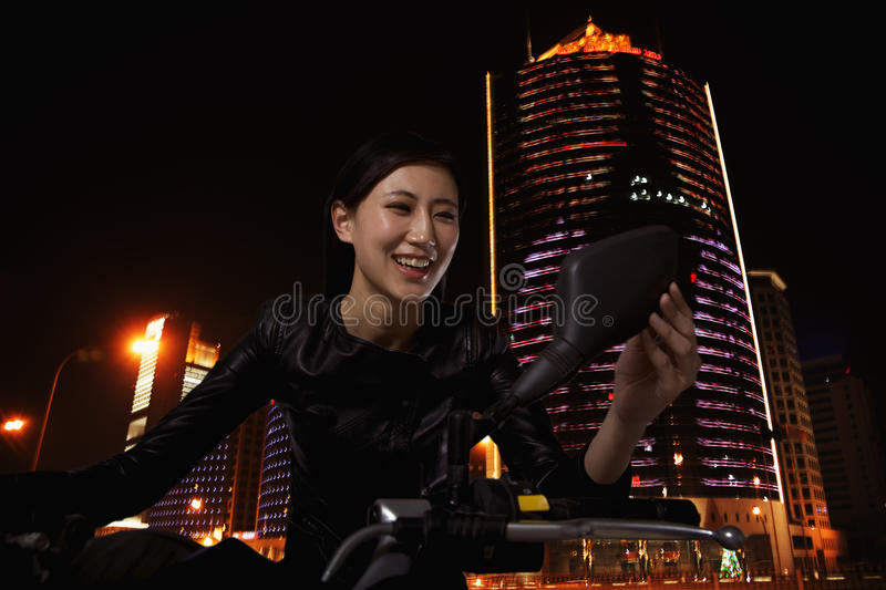 Beautiful young woman checking herself in the side mirror of a motorcycle, outdoors at night in Beijing royalty free stock image