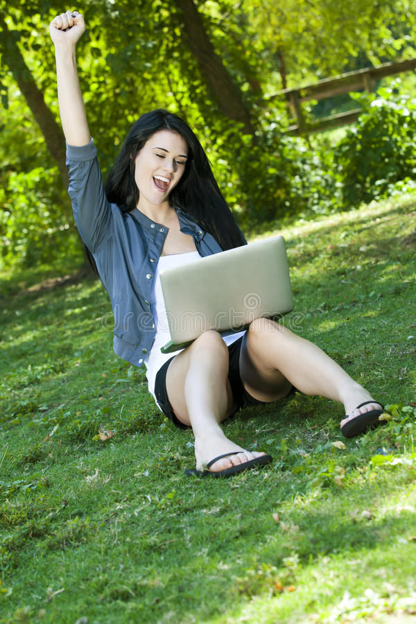 Beautiful Young Woman cheering with computer stock photos