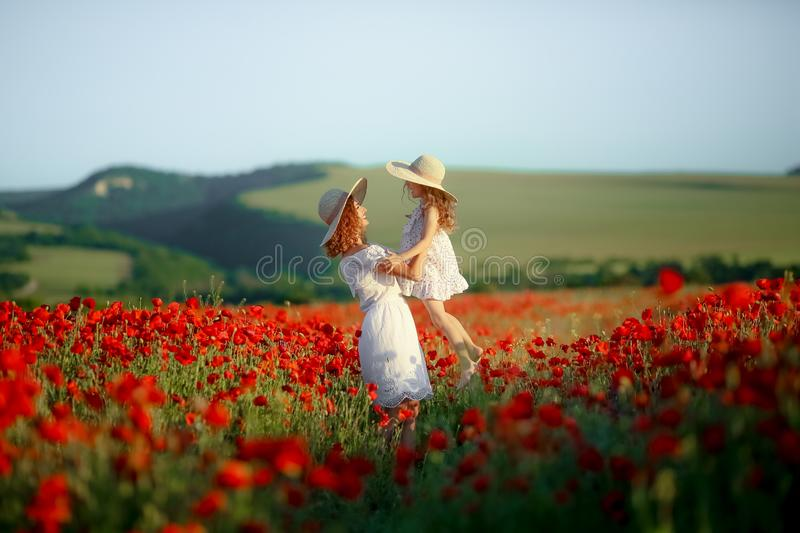 Beautiful young woman with child girl in poppy field. happy family having fun in nature. outdoor portrait in poppies stock photo