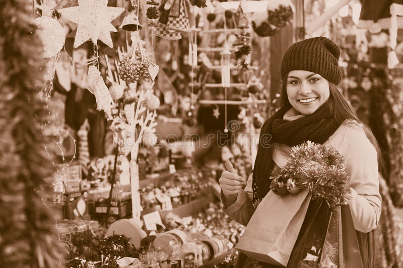 Beautiful young woman choosing Christmas decoration royalty free stock images