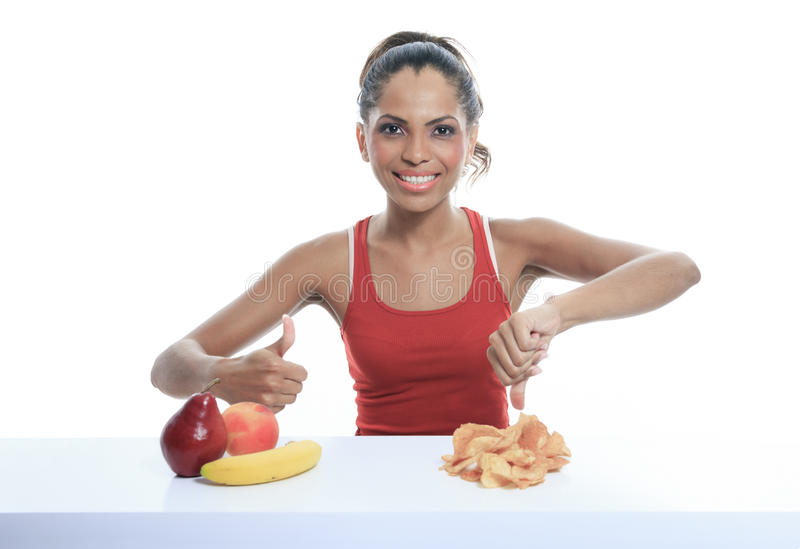 Beautiful young woman choosing between fruits and royalty free stock photo