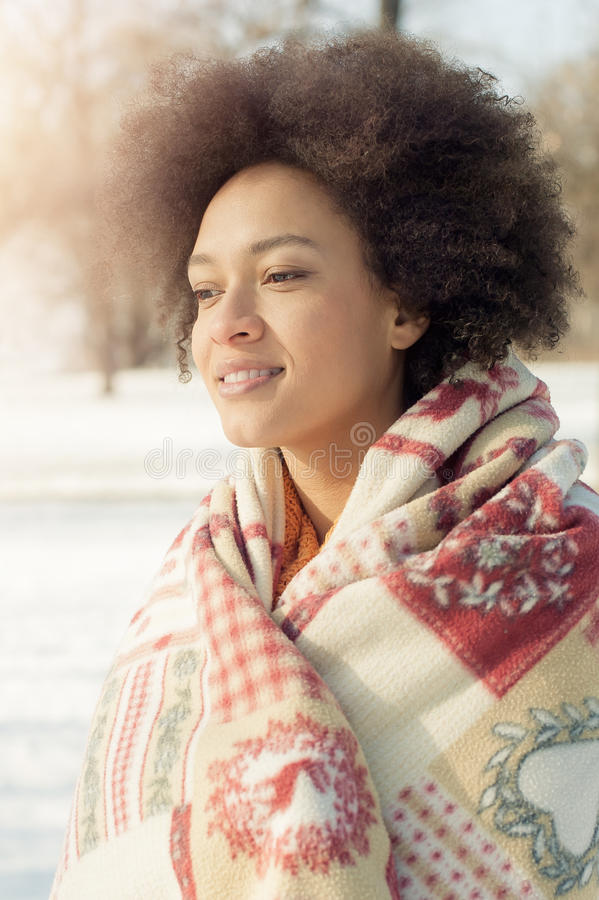 Beautiful young woman with Christmas blanket enjoying winter sun royalty free stock photos