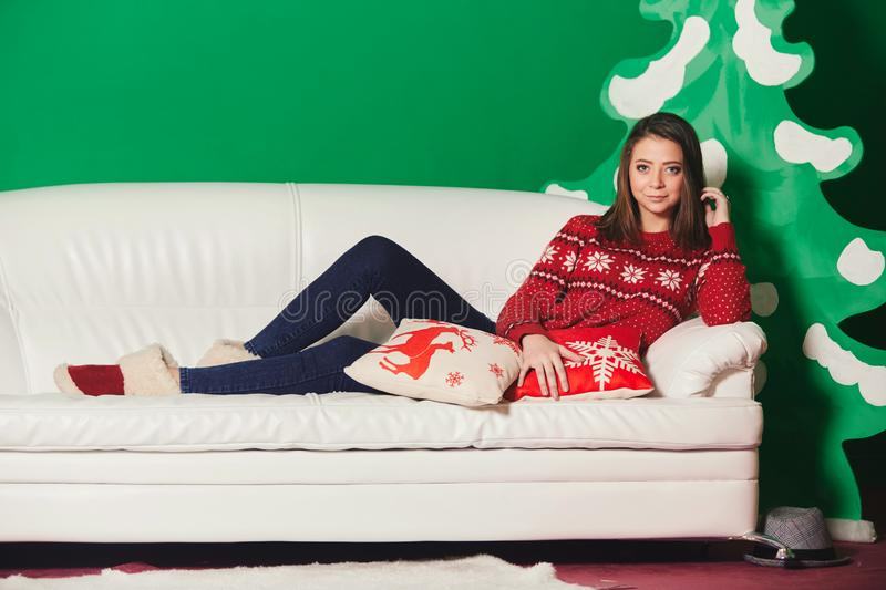 Beautiful young woman in a Christmas sweater lies on the white sofa. behind artificial Christmas decorations stock photos