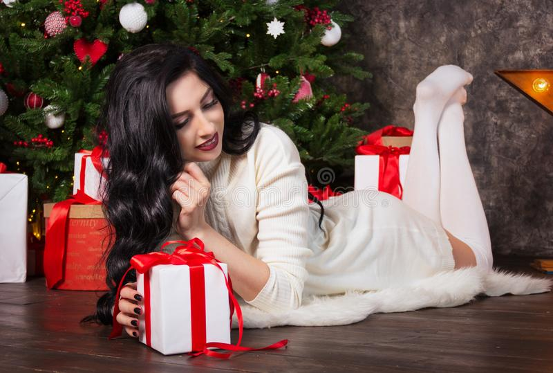 Beautiful young woman, Christmas tree and gift box. Beautiful woman opens gift stock images