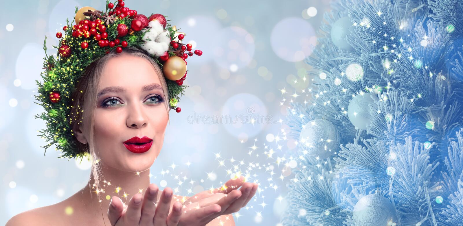 Beautiful young woman with Christmas wreath blowing magical snowy dust on blurred background. Bokeh effect stock photography