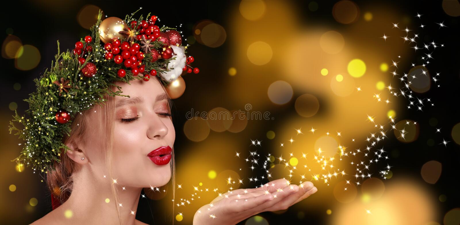 Beautiful young woman with Christmas wreath blowing magical snowy dust on color background. Bokeh effect royalty free stock images
